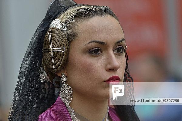 Fallas festival  woman in a traditional costume during the parade in the Plaza de la Virgen de los Desamparados  Valencia  Spain  Europe