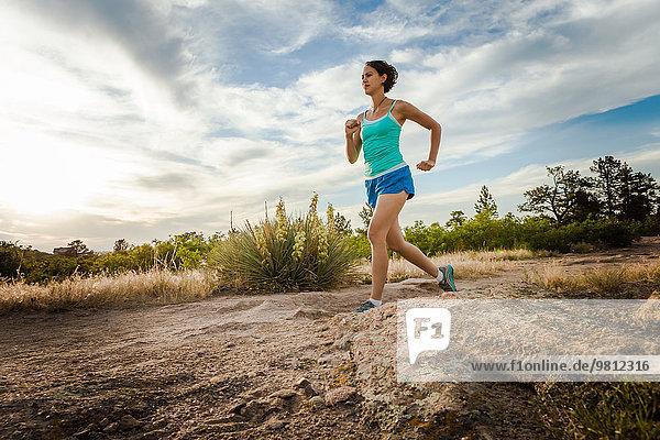 Mittlere erwachsene Frau  die auf unbefestigter Piste läuft