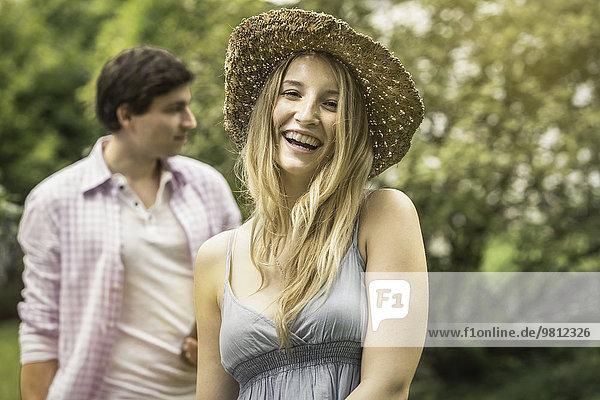 Junge Frau mit Strohhut lacht  Portrait