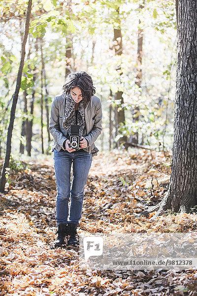 Junge Frau fotografiert Herbstlaub im Wald