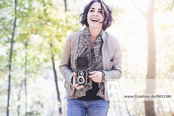 Junge Frau beim Fotografieren im Herbstwald