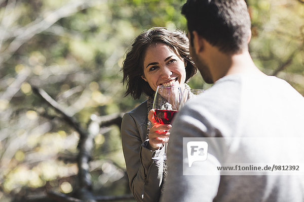 Romantic couple drinking rose wine in forest