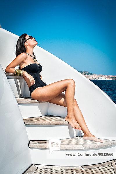 Junge Frau beim Sonnenbaden auf der Treppe
