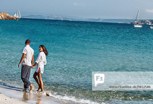 Ein Paar geht Hand in Hand am Strand entlang.
