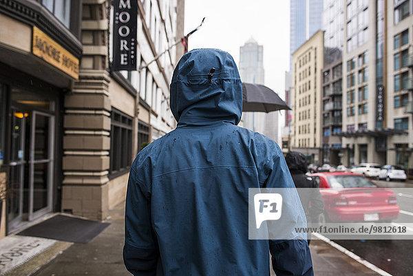 Rückansicht des jungen Mannes  der auf einer verregneten Straße spazieren geht  Seattle  Washington State  USA
