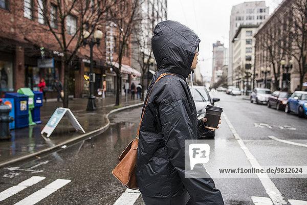 Junge Frau auf regnerischem Fußgängerüberweg  Seattle  Washington State  USA