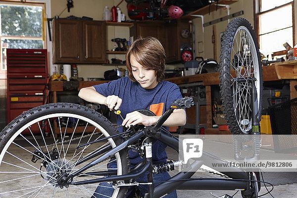 Boy repairing bicycle in garage