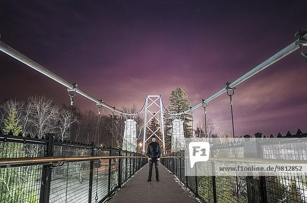 Porträt eines jungen Mannes auf einer Fußgängerbrücke  Montmorency Falls Park bei Nacht  Quebec City  Quebec  Kanada