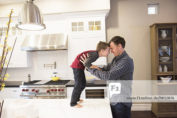 Father face to face and holding son on kitchen counter
