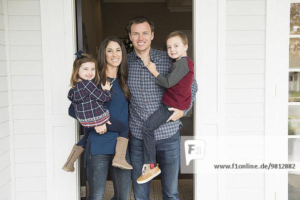 Porträt von Eltern und zwei Kindern vor der Haustür