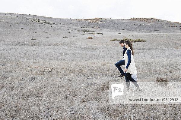 Eltern und zwei Kinder beim Wandern in hügeliger Landschaft