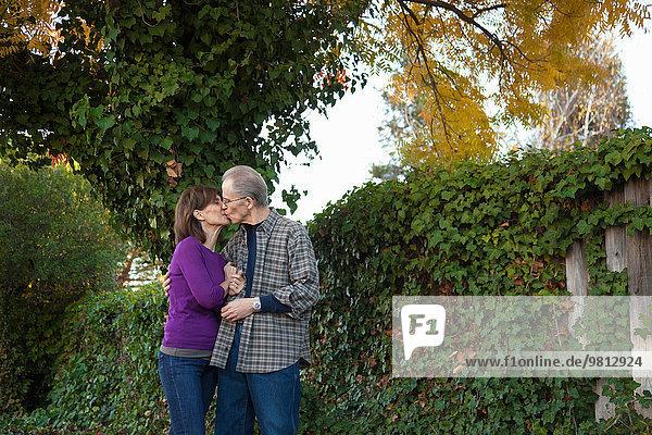 Senior couple sharing a kiss in garden