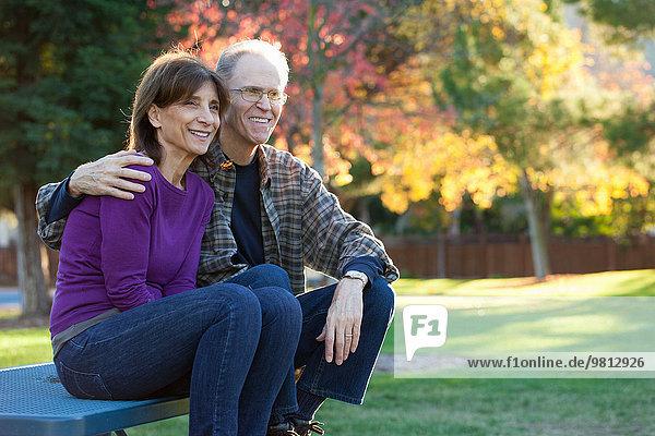 Senior couple sitting on bench in garden