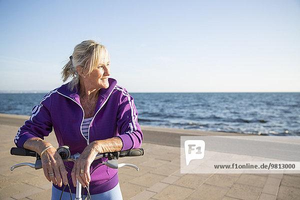 Seniorin auf dem Fahrrad am Strand