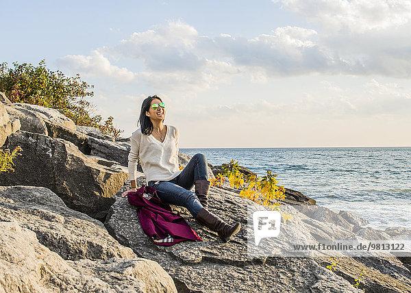 Mittlere erwachsene Frau auf Felsen sitzend