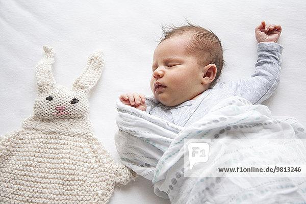 Kleines Mädchen schläft neben gestricktem Kaninchen