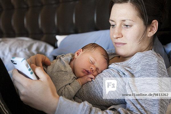 Junge Frau mit Smartphone,  Baby schläft auf der Brust