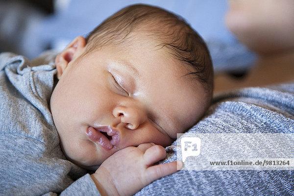 Baby Mädchen schläft auf der Brust der Mutter