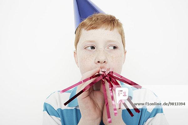 Junge mit Kegel Partyhut  der Luftschlangen bläst.