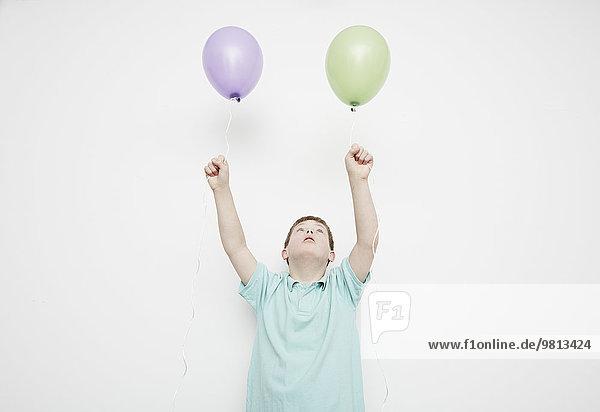 Junge hält Ballons