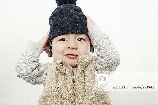 Porträt des süßen Jungen  der sich am Hut festhält Porträt des süßen Jungen, der sich am Hut festhält