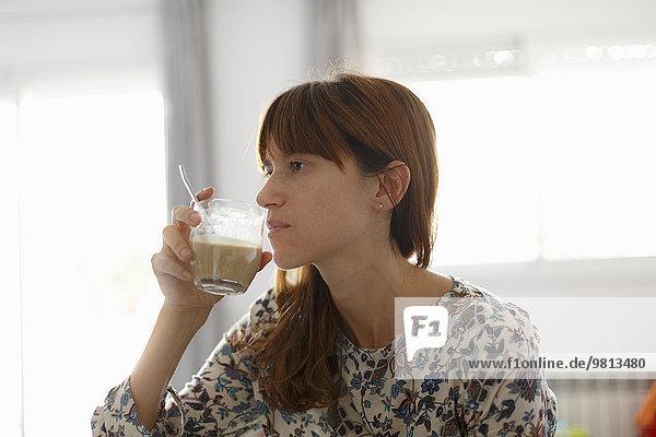Mittlere erwachsene Frau beim Kaffeetrinken in der Küche