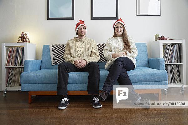 Porträt eines jungen Paares mit Weihnachtsmützen auf dem Sofa im Wohnzimmer