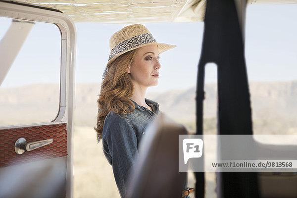 Frau steht neben dem Flugzeug