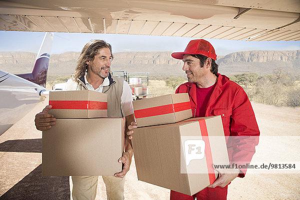 Auslieferer mit Paketen aus dem Flugzeug