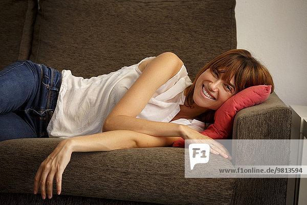 Porträt einer mittleren erwachsenen Frau  die auf einem Sofa im Wohnzimmer liegt.