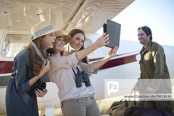 Touristen  die Selfie mit digitalem Tablett neben dem Flugzeug nehmen  Wellington  Western Cape  Südafrika