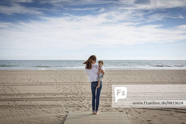 Rückansicht der mittleren erwachsenen Frau mit Kleinkind-Tochter am Strand  Castelldefels  Katalonien  Spanien