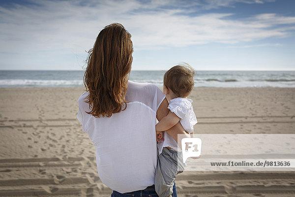 Rückansicht der mittleren erwachsenen Frau und Kleinkindstochter mit Blick aufs Meer  Castelldefels  Katalonien  Spanien