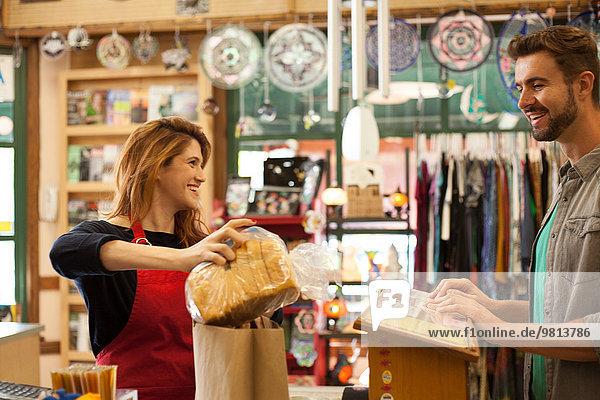 Verkäuferin beim Verpacken von Brot für Einkäufer im Reformhaus