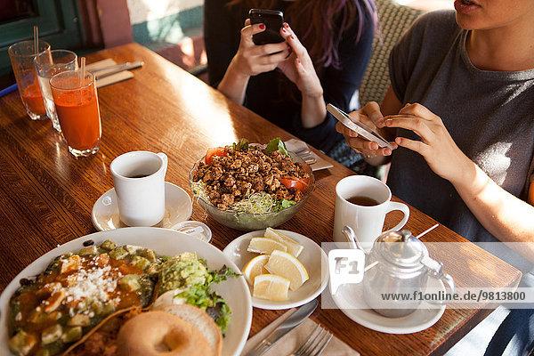 Ausschnittaufnahme von weiblichen Freunden  die auf Smartphones im vegetarischen Restaurant texten.