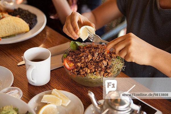 Ausgeschnittene Aufnahme einer Frau  die Zitrone beim Essen im vegetarischen Restaurant drückt.