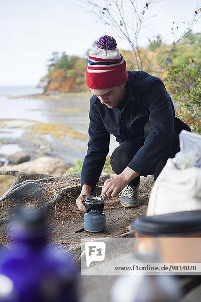 Männlicher Wanderer zündet Campingkocher am Flussufer  Rangeley  Maine  USA