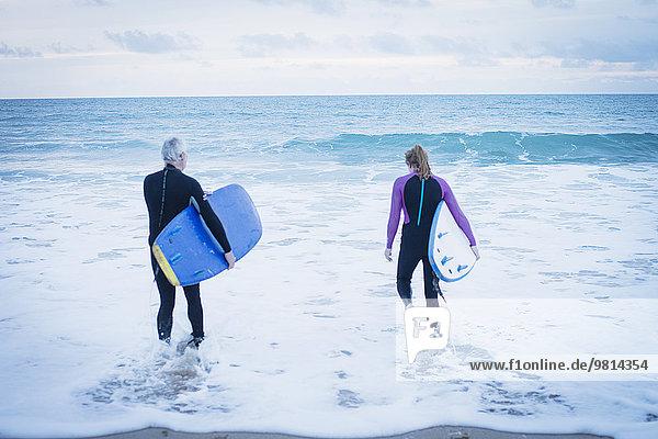 Vater und Tochter mit Surfbrettern im Meer