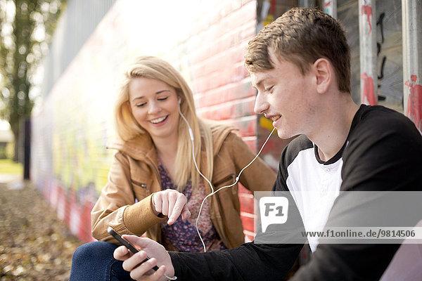 Teenager-Paar hört mp3-Player gegen die Wand mit Graffiti