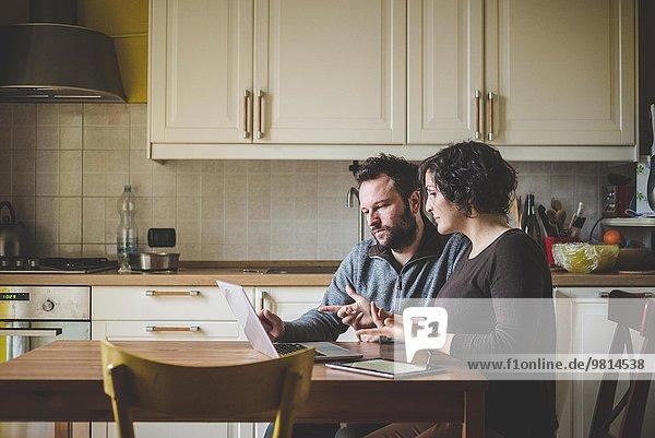 Paar am Tisch sitzend  mit Laptop