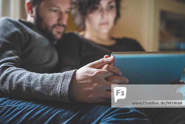 Paar sitzt auf dem Sofa und schaut auf das digitale Tablett.