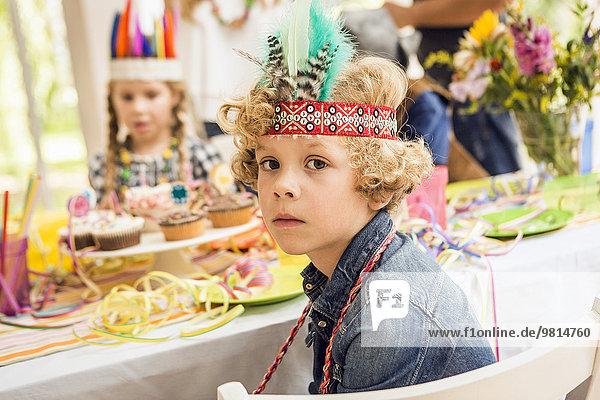 Porträt eines ernsthaft aussehenden Jungen auf einer Kindergeburtstagsparty