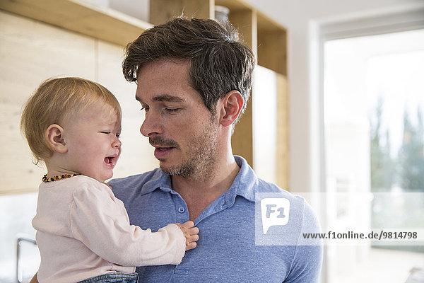 Weibliches Kleinkind weint in den Armen des Vaters in der Küche