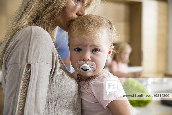 Portrait des weiblichen Kleinkindes in den Armen der Mutter in der Küche
