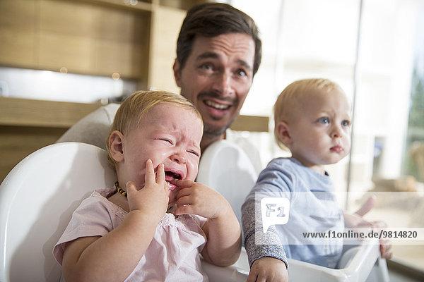 Vater zwischen männlichen und weiblichen Zwillingskindern in Hochstühlen
