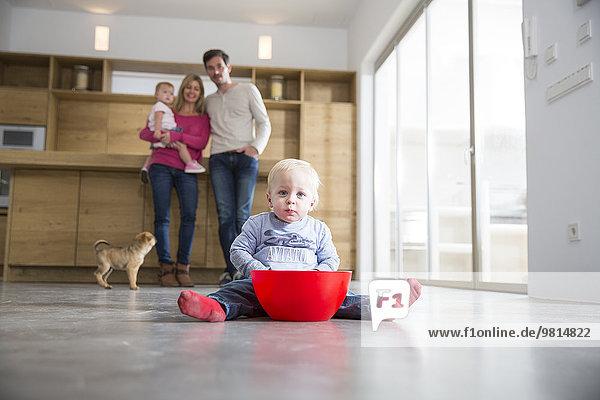 Familie beobachtet männliches Kleinkind mit Schüssel auf dem Boden des Esszimmers