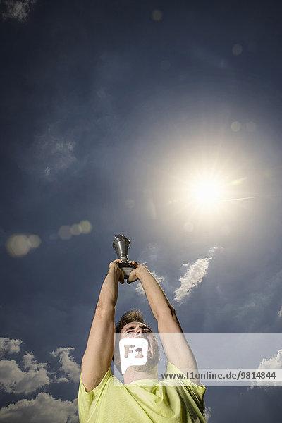 Junger männlicher Sportler feiert Siegerpokal
