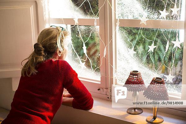 Mutter schaut aus dem Fenster mit Weihnachtsschmuck