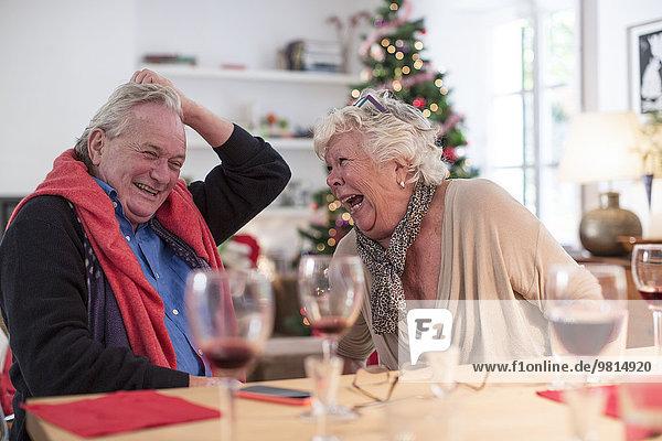 Seniorenpaar lacht am weihnachtlichen Mittagstisch