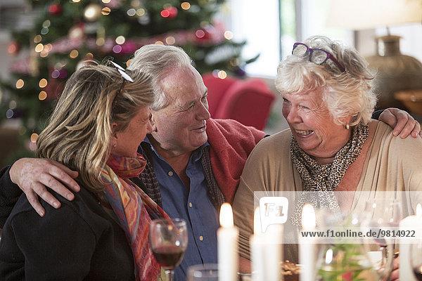 Seniorenfamilie lacht am Weihnachtstisch